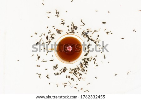 Photo of Cup of tea with tea herbs around and a flower. Food background or healthy concept with white background