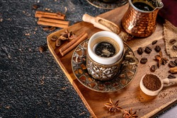 Cup of turkish coffee on black background with spices, coffee beans and sand coffee pot