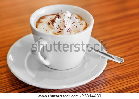 Cup of whipped cream coffee on the wooden table