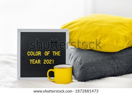 Cup or mug with tea or coffee and pillows on bed in bedroom Illuminating Yellow and Ultimate Gray. Board with yellow text color of the year 2021.