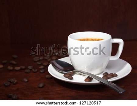 cup, saucer with spoon and coffee beans on wooden table