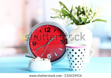 Cup tea and clock on bright background