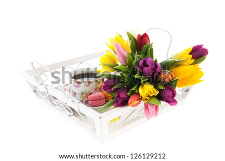 cup tea in cheerful cup with macaroons and flowers on white tray