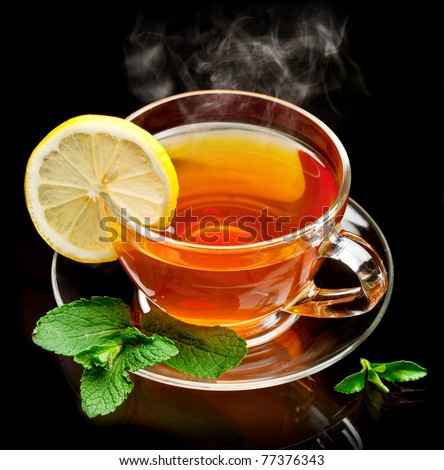 Cup tea with mint and lemon isolated on a black background.
