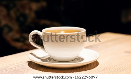 Cup with aromatic coffee on a wooden table