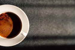 Cup with aromatic hot coffee.Creamy cup of black coffee.Classic filter arabica drink.Espresso americano.Favorite hot beverage.Morning sunrays on the table.Caffeine energy.Gray copy space.