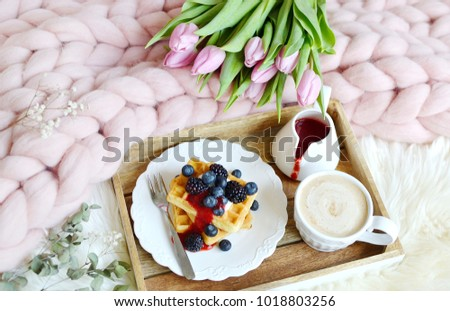 Cup with cappuccino and homemade Belgian waffles with strawberry sauce and berries, pink pastel giant blanket, fur, bedroom, pink flowers tulips, spring, woman day morning concept