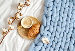 Cup with cappuccino, croissant, blue pastel giant plaid, bedroom, morning concept, cotton flower top view