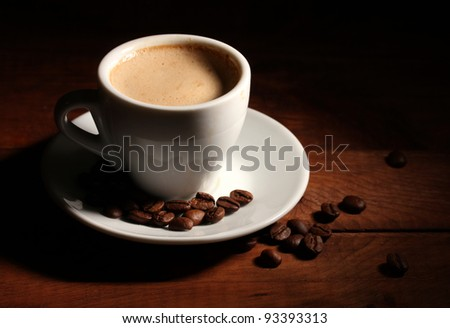 cup with coffee and coffee beans on  wooden table