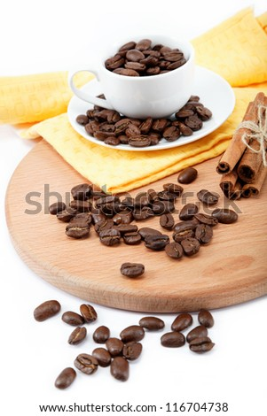 Cup with coffee beans and a bunch of cinnamon on a wooden board.