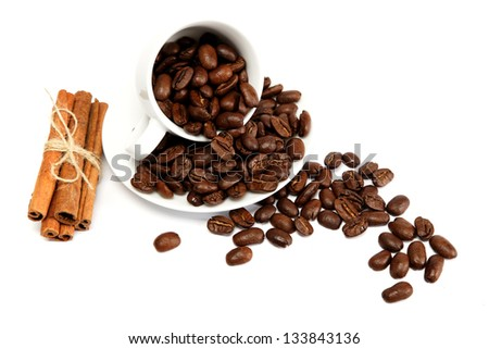 Cup with coffee beans isolated on white background.
