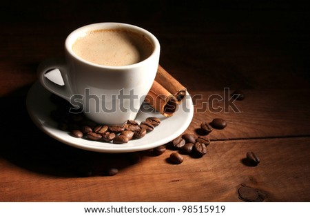 cup with coffee, cinnamon and coffee beans on  wooden table