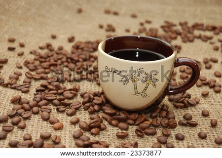 Cup with coffee. Fried beans at background