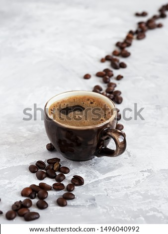 Cup with dark espresso arranged on a gray background. Roasted coffee beans are located around a cup of coffee.