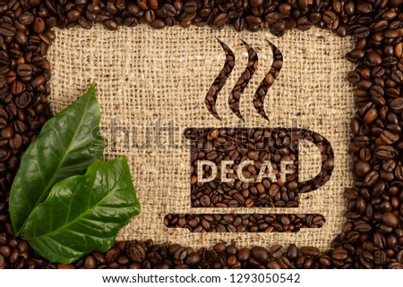 Cup with decaf text written as aroma of no-caffeine hot beverage inside scattered coffee beans frame on brown burlap bag background