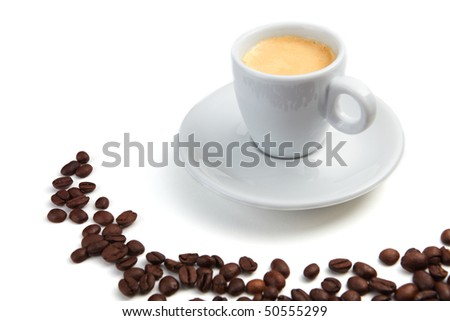Cup with espresso surrounded by coffee beans