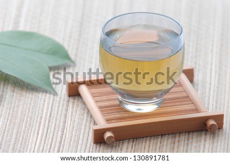 Cup with green tea and green leaves