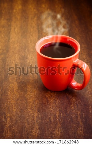 Cup with hot black coffee over wooden background