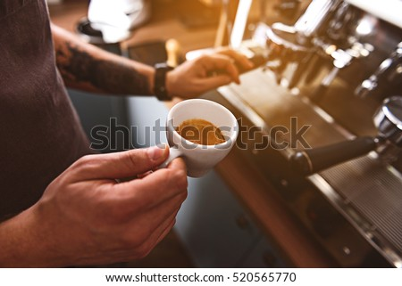 cup with hot cappuccino in man hands #520565770