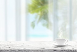 Cup with hot drink on wooden table and blue seascape on a background. Beauty nature background
