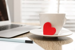 Cup with red heart on table, space for text. Valentine's day celebration