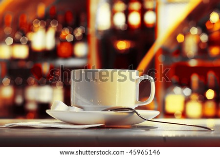 Cup with tea and sugar on plate in night club