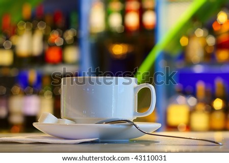 Cup with tea on table in night club