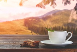 Cup with tea on table over mountains landscape with sunlight. Beauty nature background.