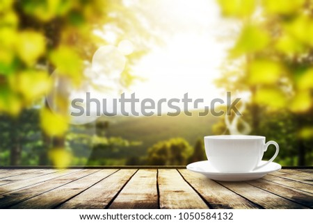 Cup with tea on table over mountains landscape with sunlight. Beauty nature background #1050584132