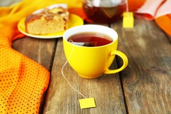 Cup with tea, teapot and tea bags on wooden table close-up