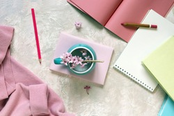 Cup with water and fresh hyacinth flowers, books, notepads, woolen pink sweater on a light background, at home, romantic congratulation, emotion of love
