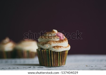 Cupcake decorated with cream, chocolate and heart shape candies on wooden table. #537404029