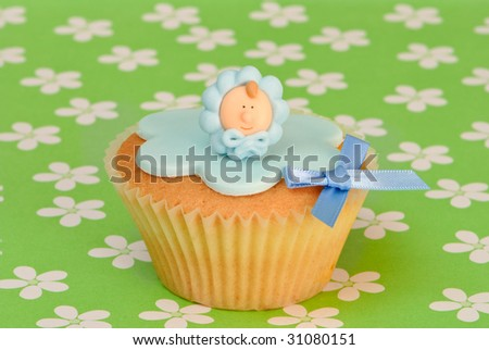 Cupcake decorated with icing and baby boys face