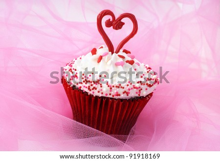 Cupcake decorated with sprinkles and a red chocolate heart