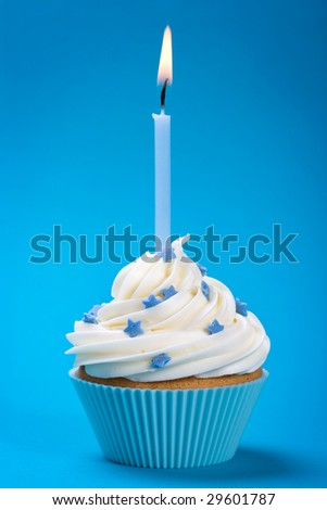 Cupcake decorated with sugar stars and a single blue candle - stock photo