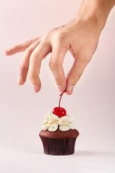 Cupcake decoration. Hand decorating cupcake adding cherry on top.