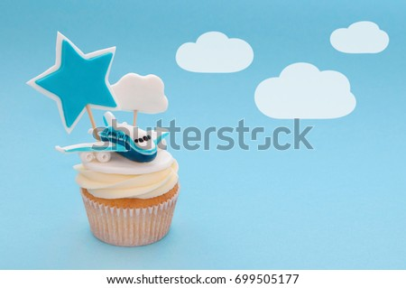Cupcake for boy with whipped cream, decorated plane, toppers star and cloud on blue background. Picture for a menu or a confectionery catalog.