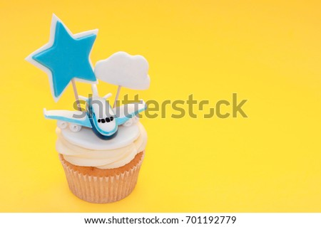 Cupcake for boy with whipped cream, decorated plane, toppers star and cloud on yellow background. Picture for a menu or a confectionery catalog.