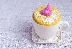cupcake in a mug cooked in the microwave. White cup on a square small plate. Homemade simple baking concept. High quality photo