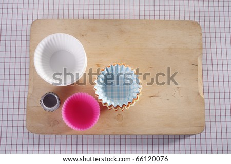 Cupcake molds on chopping board.