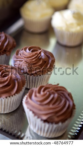 cupcake on a tray. small dessert muffin cakes with frosting on top #48764977