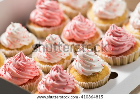 Cupcake packaging, delivery box, vanilla cupcakes with pink and white cream, selective focus, close up