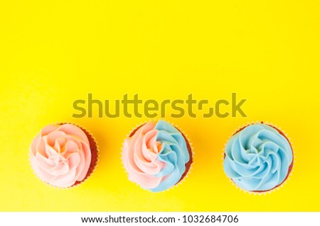 Cupcake red velvet with blue and pink whipped cream on yellow background. Picture for a menu or a confectionery catalog. Top view.