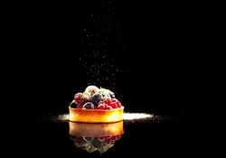 Cupcake with berries sprinkled with icing sugar on black background, close up, copy space