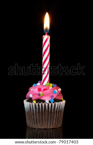 cupcake with burning candle over black background