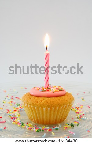 Cupcake with candle on glass plate with candy sprinkles - stock photo