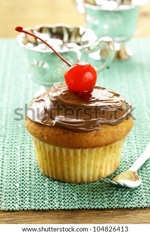 cupcake with chocolate cream on a wooden table