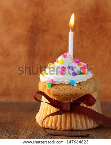 Cupcake with cream and candles - happy birthday