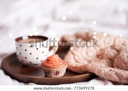 Stock Photo Cupcake with cup of coffee with knitted cloth on wooden tray in bed close up. Good morning.