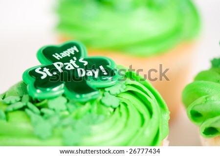 Cupcake with green icing and Happy St-Pat\'s Day written on it. It is on a white background with other cupcakes in the background.